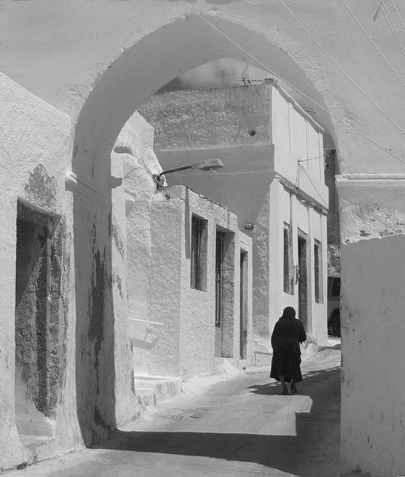 Woman walking under arch in traditional village of Megalochori.