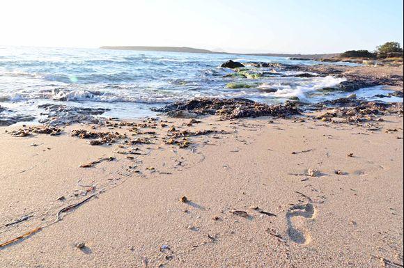 Sunrise waves, footprint in the sandy beach