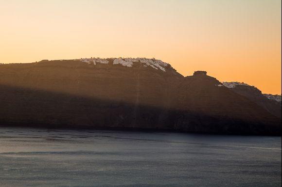 Sunrise lighting up the silhouette of Sakros Rock, Imerovigli