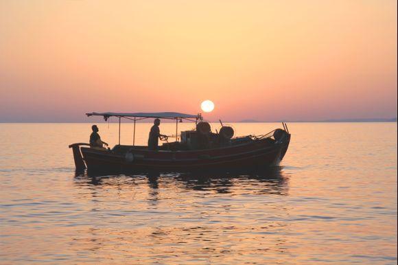 Elounda, fishermen working as the sun rises.