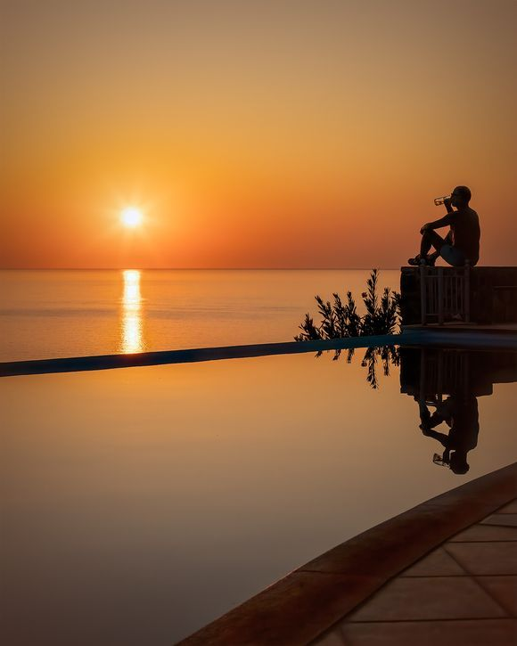Cool beer and hot sunset by the infinity pool, Molyvos.