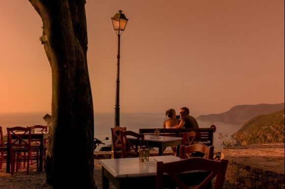 Young lovers watching the sunset over the old town