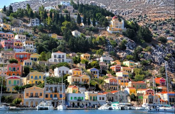 Symi island: a perfectly painted image of a scenic traditional village! Symi island has one of the most impressive ports in the Greek islands, with elegant mansions constructed amphitheatrically on the slopes of a hill and offering breathtaking view to the sea from any spot.