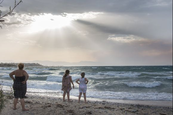 Mother watches daugters in windy sunset in Agistri.