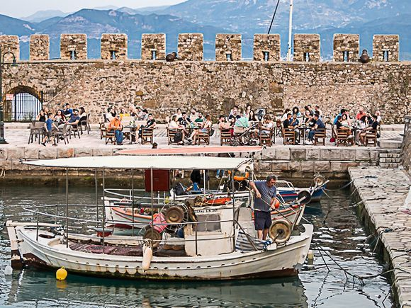 Ancient harbor with fisherman arriving and cafe crowd watching.
