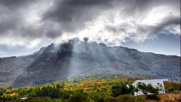 The sun breaks through the clouds over Kalí Límni.