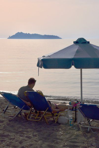 Tourists enjoying the late afternoon sun on the beach in Petros, on the island of Lesvos.