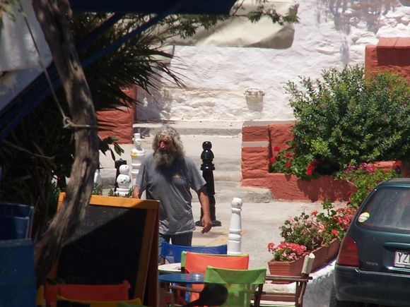 Delapizza tending to the chess board in front of his studio.  Shot from a distance while sitting on Rolando\'s deck.  Thank you Delapizza for all that you do for the village and the people of Ioulis!