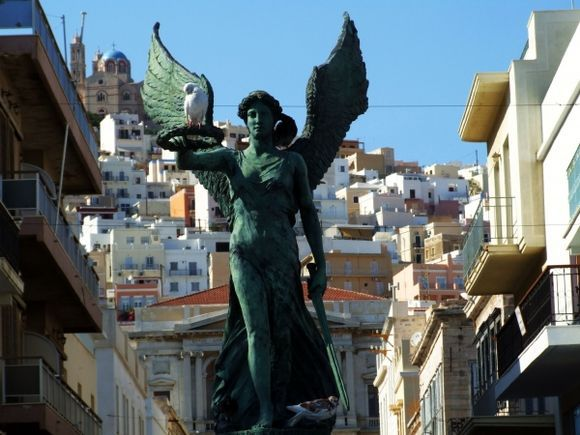 to Ermoupoli town, Syros island, the freedom statue, with pigeons are taking a break