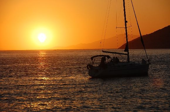 A sailing boat stands on the sunset. Katapola, Amorgos