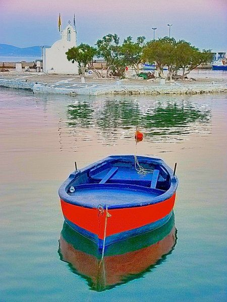Red boat anchored in the port of the island of Naxos