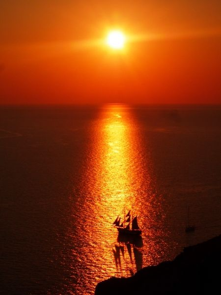 Sailboat in sunset light from Oia