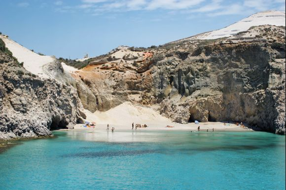 <b>Tsigrado</b> is one of the most beautiful southern beaches of Milos island. Located right next to Firiplaka, Tsigrado is a small sandy cove with crystal water. Going down this beach is a bit difficult as visitors have to pass through a rocky passage and climb down a wooden ladder to get there. The surrounding environment with the rocky cliffs is quite impressive and totally worth it!  Check out the best beaches of Milos here: https://www.greeka.com/cyclades/milos/beaches/