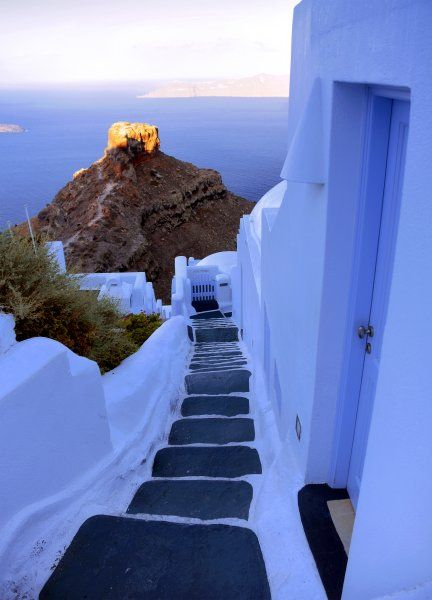 Stairway to light (The famous Skaros Rock at Imerovigli illuminated by the morning sunrays)