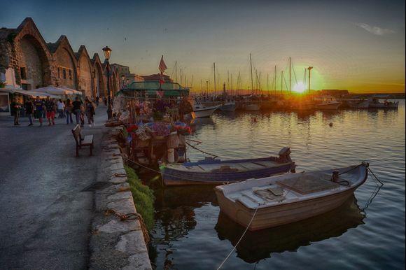 Evening Chania harbor scene at sunset.