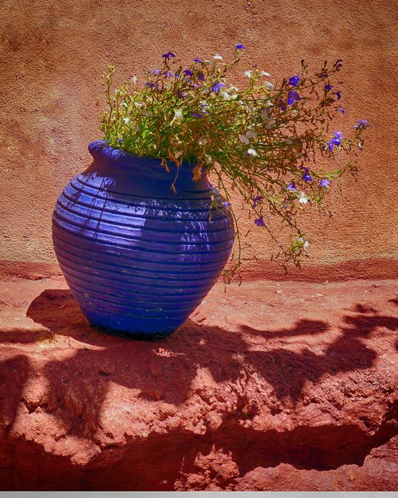 Narrow Street Blues -A blue flower pot with blue and white flowers in a narrow alley of Chania's Old Town area.