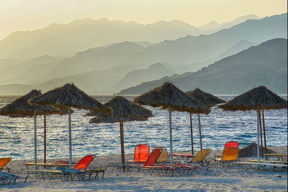 Umbrellas and lounge chairs line the Triopetra beach at the end of the day with the rugged foothills of Crete's southern coast as a backdrop.