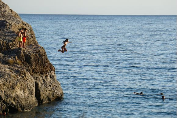Young people enjoying the thrill of jumping from the rocks at Psilos Bolakas (Tall Rock) Beach near the town of Paleochora.