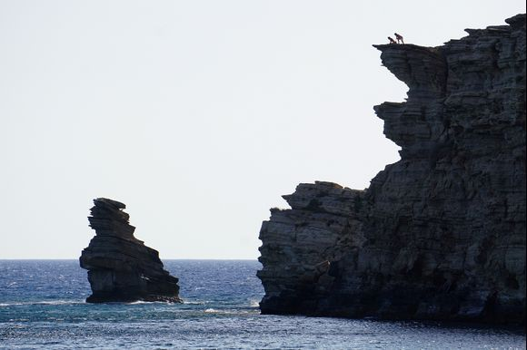 A couple of visitors on top of the Triopetra rocks cautiously lean over for a better look.