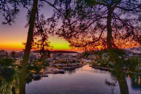 A peaceful morning view of Agios Nikolaos' Lake Voulismeni just before sunrise.