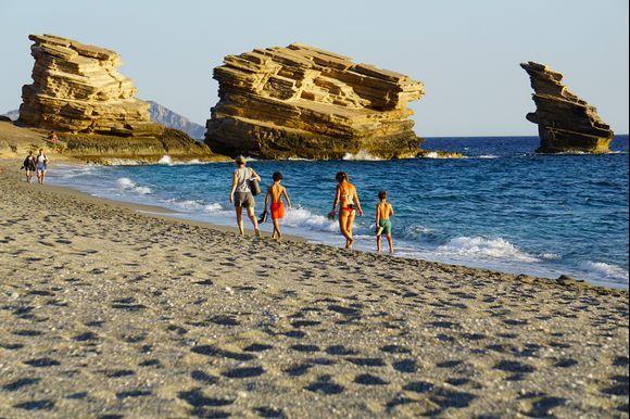 Visitors walk along the picturesque Triopetra (Three Stones) beach on Crete's southern Libyan Sea coast.