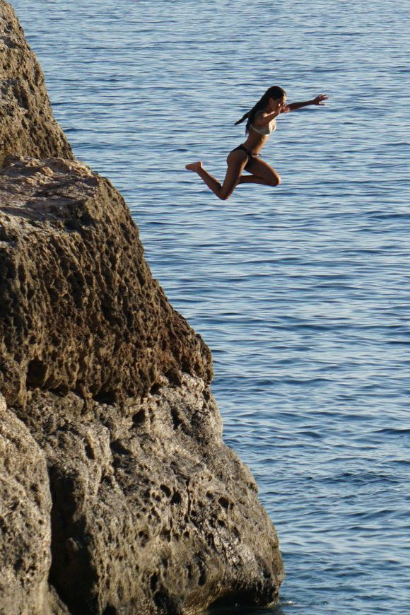 A young woman jumps from the rocks at Psilos Bolakas (Tall Rock) Beach near the town of Paleochora.