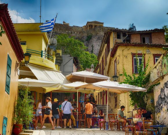Visitors relax on a narrow street in Plaka under the slope of the Acropolis hill.