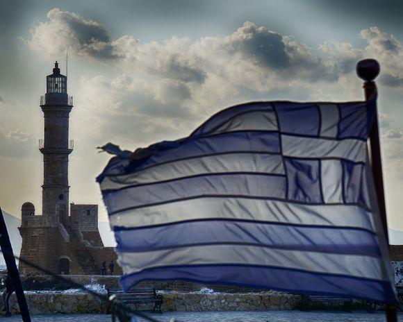 A wind-whipped Greek flag flies on a sailboat near the Chania harbor's Venetian lighthouse.