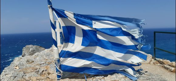 Greek flag on the top of Kastro on a windy day