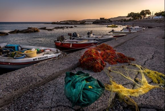 Fishermen's nets and boats resting at the port in Kiotari