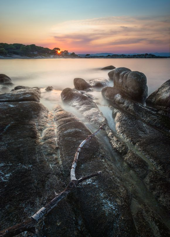 A long exposure of the sun setting over Karidi beach with some lovely rocks and a stick in the foreground.