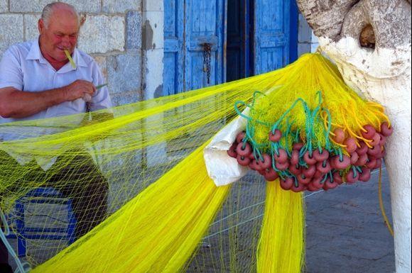 Fisherman mending yellow nets