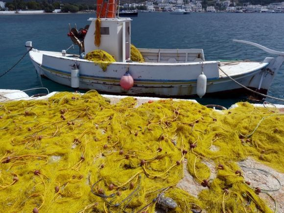 Fishing boat and yellow fishnets in the bay of Katapola