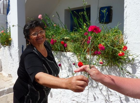 Woman offering a carnation to a passer-by in Koronos village