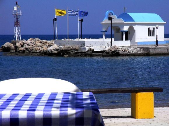 Waterfront with Agoi Apostoloi small church and taverna table, Faliraki