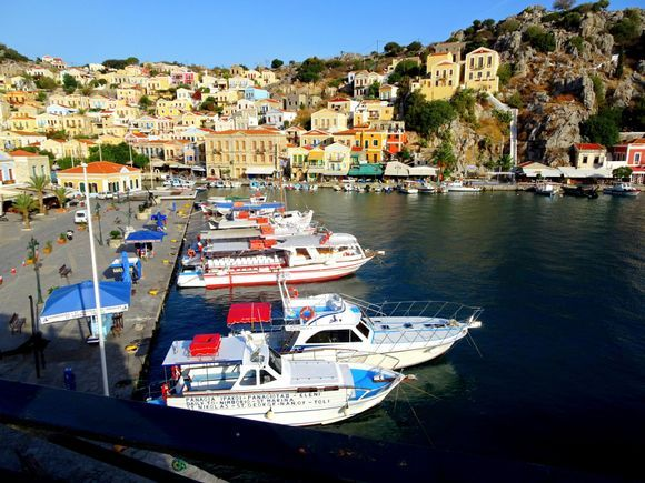 Scenery with neoclassical houses and excursion boats. Gialos