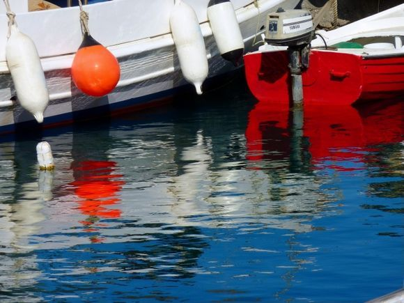 Red boat, buoys and reflections