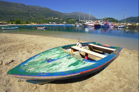 Sandy beach with colorful boats and reflections