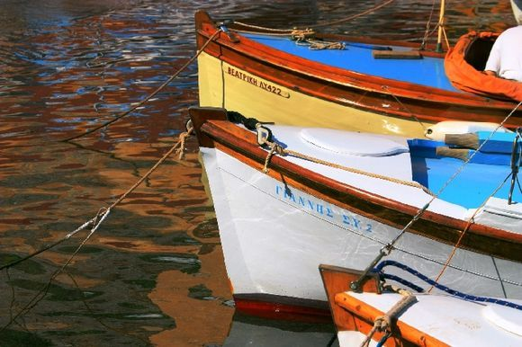 Hydra town harbour with colorful boats and reflections