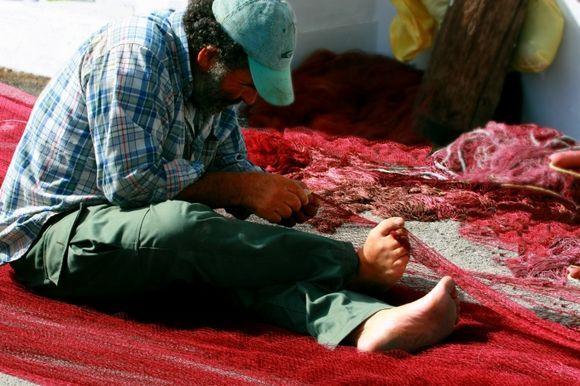 Fisherman mending red nets