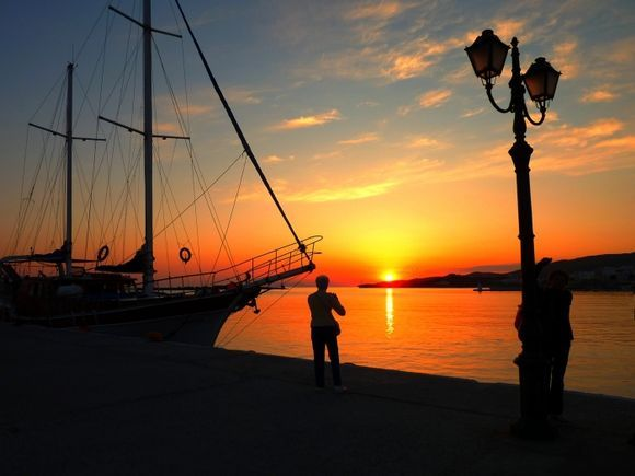 People, sail and lamp post at sunset on Tinos waterfront