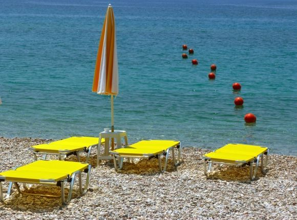 Pebble beach with sunbeds and red buoys
