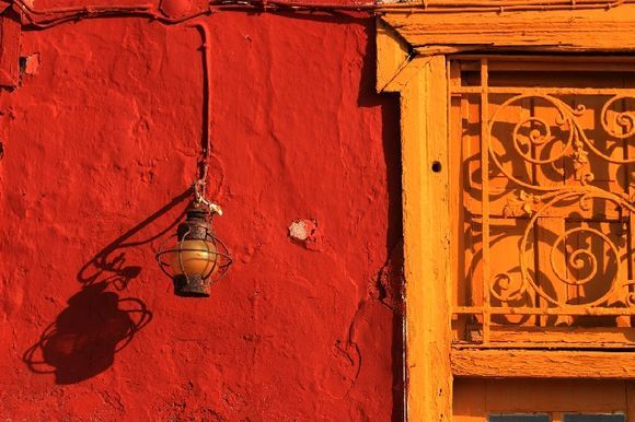 Red wall with old lamp and yellow door