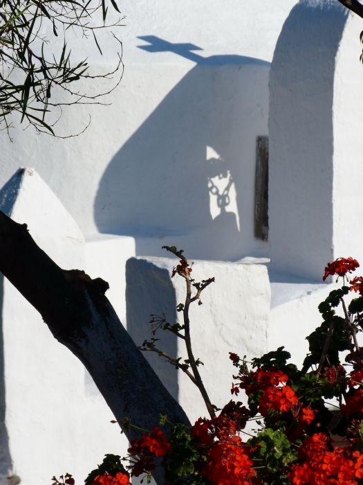 Facade of small church with shadows and geranium