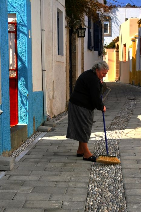 Village street with woman sweeping
