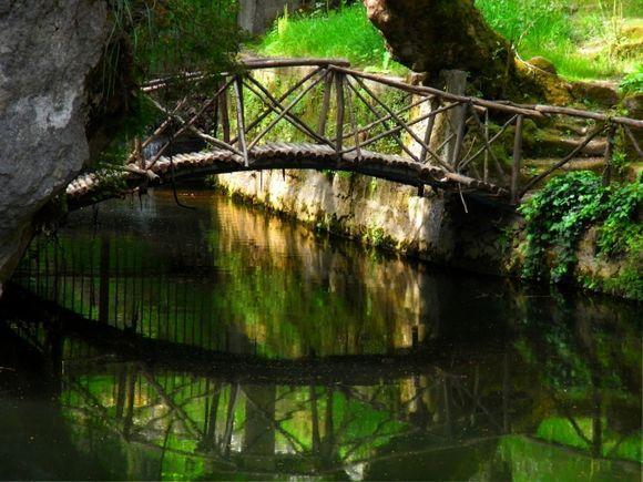 Wooden bridge and reflections. Rodini park