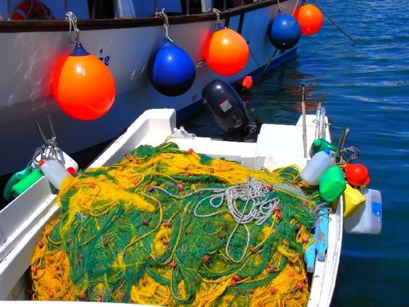 Fishing boat with multicolored buoys and fishing nets in Faliraki small harbour