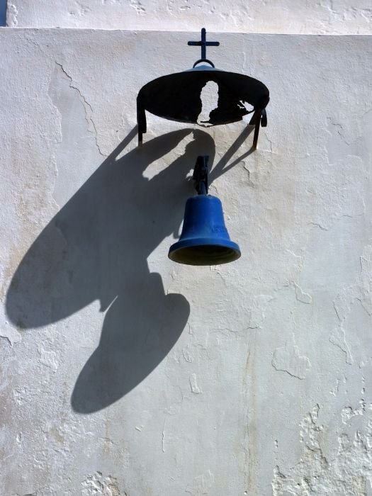 Apokrousi church wall with bell and shadows