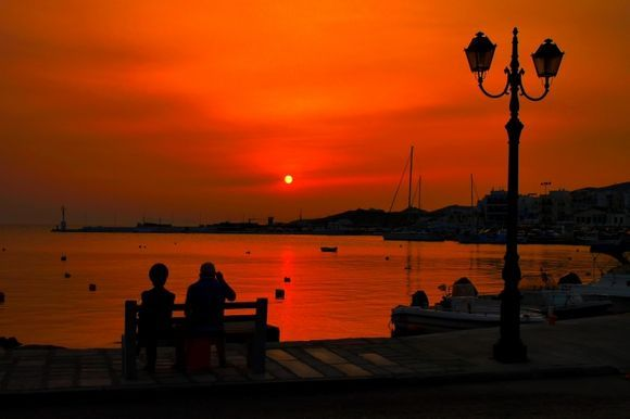 Couple sitting on a bench near the water at sunset