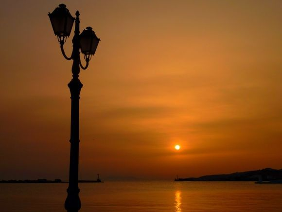 Sunset in Tinos town harbour with lamp post
